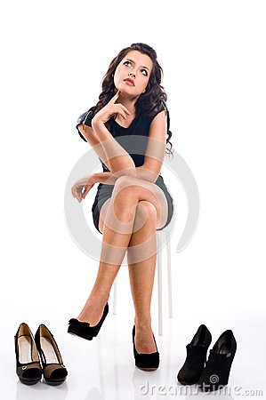 Beautiful young woman with long hair chooses shoes