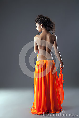 Beautiful young woman in long orange skirt