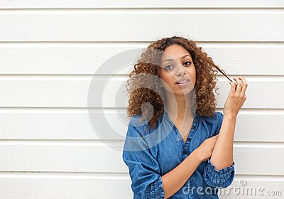 Beautiful young woman looking at camera with hand in hair