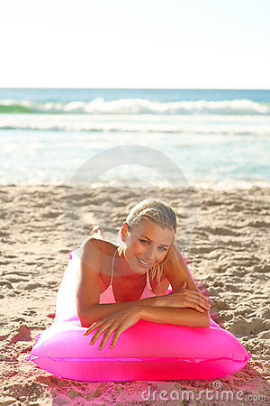 Beautiful young woman lying on a pink water float