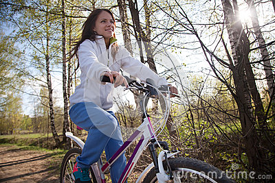 Beautiful young woman with mountain bicycle in spring forest Stock Photo