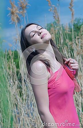 Beautiful young woman in pink dress enjoying wind