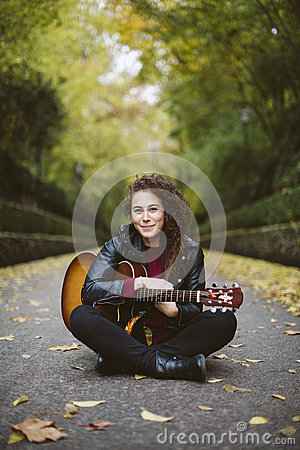 Free Beautiful Young Woman Playing Guitar Sitting On The Forest. Royalty Free Stock Image - 86389396