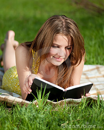 Beautiful young woman reading book outdoor