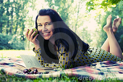 Beautiful young woman reading outdoor