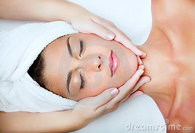 Beautiful young woman receiving facial massage.