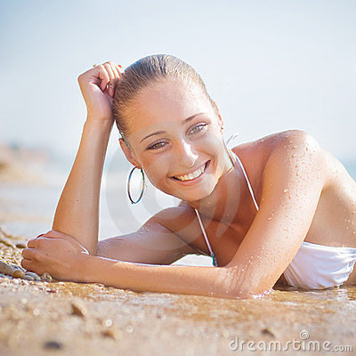 Beautiful young woman on the sand on the seashore