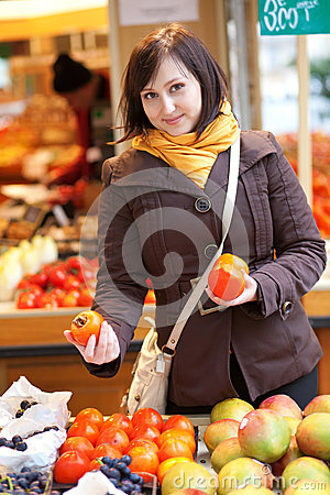 Free Beautiful Young Woman Selecting Date Plums Royalty Free Stock Image - 26210876