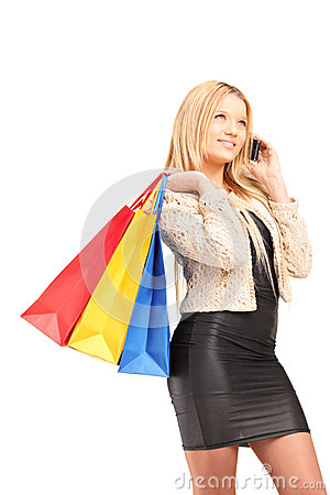Beautiful young woman with shopping bags talking on a phone