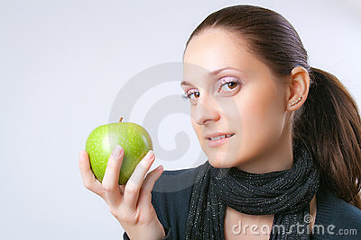Beautiful young woman showing an apple