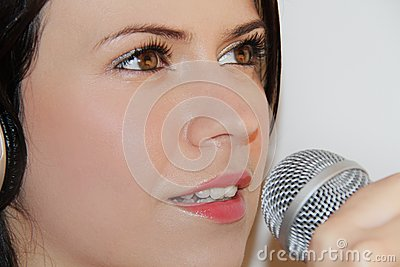 Beautiful young woman singing and listening to music with headphones