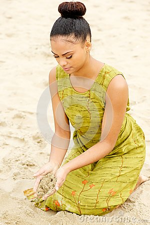 Beautiful young woman sitting at the beach with sand flowing from hands