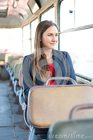 Beautiful young woman sitting in bus