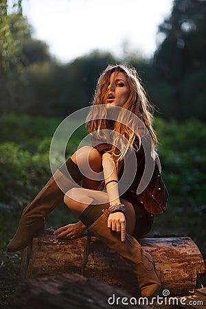 Beautiful Young Woman sitting on log