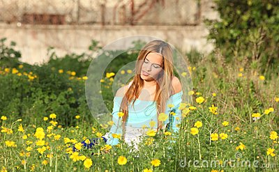 Beautiful young woman sitting in meadow