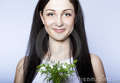 beautiful young woman smiling holding green dill