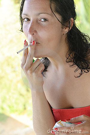 Beautiful young woman smoking cigarette