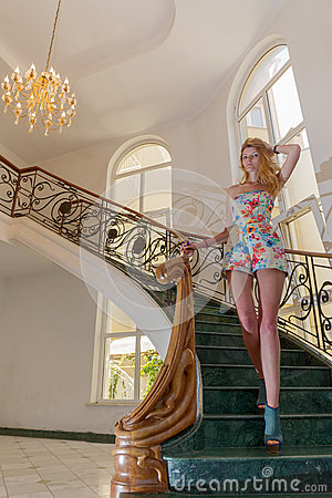 Beautiful young woman on staircase Stock Photo