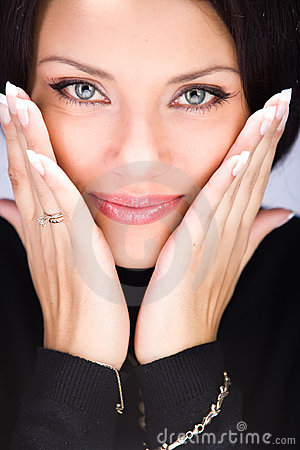 Beautiful young woman touching her face by hands