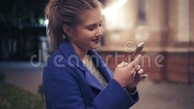 Beautiful young woman using her smart phone late at night in the city. Attractive girl texting, surfing on internet. Night street lights. Slowmotion shot stock video