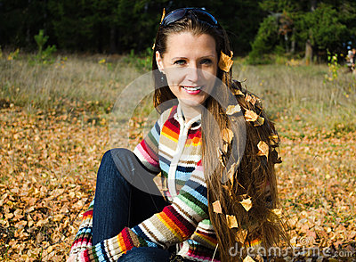 The beautiful young woman on walk in the autumn