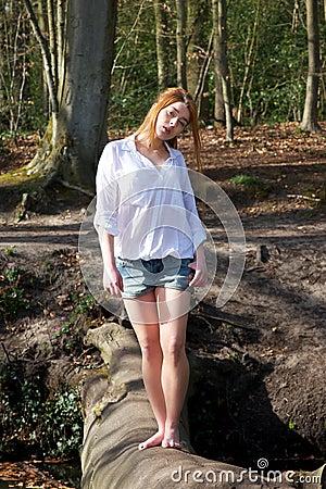 Beautiful young woman walking across a log over creek