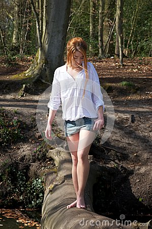 Beautiful young woman walking across a log over stream