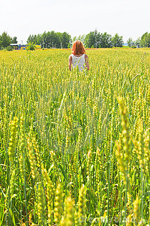 Beautiful young woman walking at wheat field