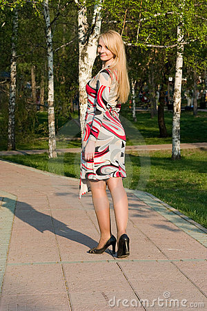 The beautiful young woman walks on park.