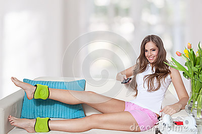 Beautiful young woman watching tv while doing leg exercises