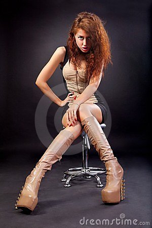 Beautiful young woman wearing boots on black