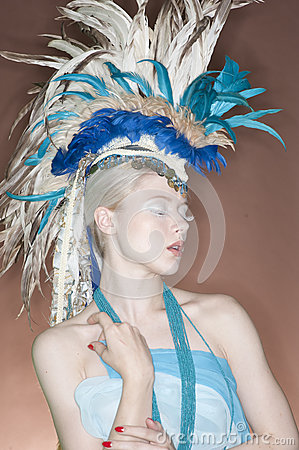 Beautiful young woman wearing feather headgear with eyes closed