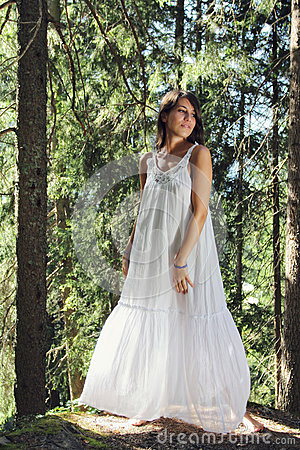 Beautiful young woman white dressed in the forest