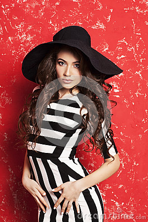 Free Beautiful Young Woman With Long Curly Hair In Black Hat And Striped Dress On Red Background. Stock Images - 55507044