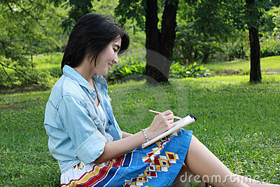 Beautiful young woman writing outdoors in a park
