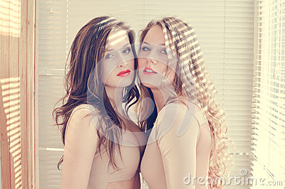 2 beautiful young women girl friends in bodily costumes with red lips standing against sun lighting