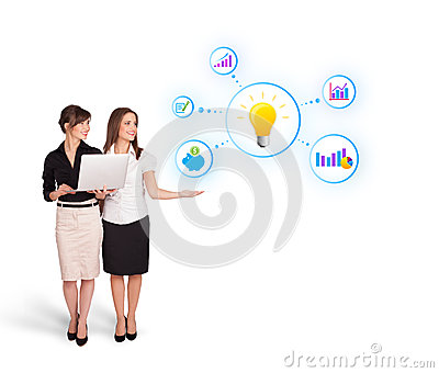 Beautiful young women presenting light bulb with colorful graphs