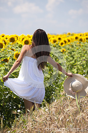 Beautifull girl playing near sunflower field