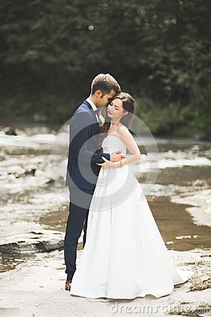 Free Beautifull Wedding Couple Kissing And Embracing Near The Shore Of A Mountain River With Stones Royalty Free Stock Photography - 108255827