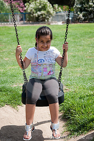 Beautifull young girl playing on the swings