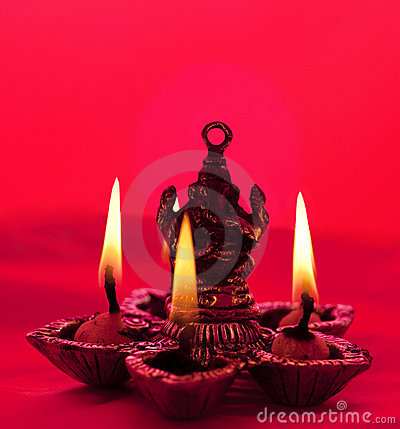 Beautifully lit lamps around Lord Ganesh