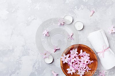 Beauty, aromatherapy and spa background with perfumed pink flowers water in wooden bowl and candles on stone table. Flat lay. Stock Photo