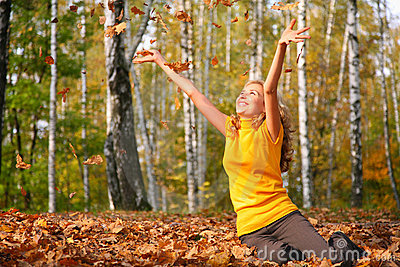 Beauty blond girl throws leaves in park