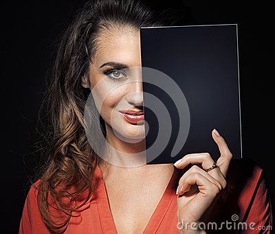 Beauty brunette hiding half of face behind black panel
