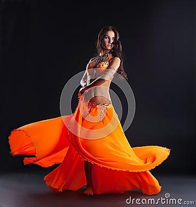 Beauty dancer posing in traditional orange costume