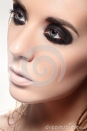 Beauty portrait of model face with fashion dark smoky-eye make-up