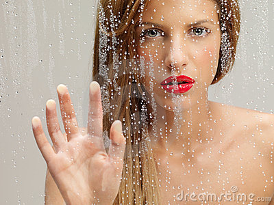 Beauty portrait of woman touching wet window