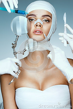 Free Beauty Victim Wrapped In Medical Bandages While Doctors With Syringes, Scalpels And Magnifying Glass Near Her Face. Stock Photos - 79415643