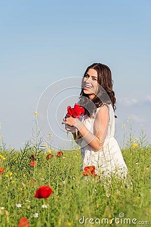 Beauty woman in poppy field in white dress holding a poppies bouquet