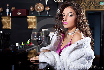 Beauty woman in white fur coat stand at bar